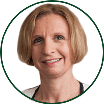 COO Katy Spink headshot, smiling and outlined in Dark Horse green color